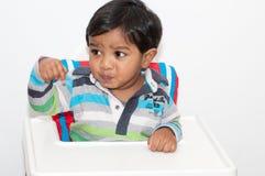 Bebé en una alta silla Fotos de archivo libres de regalías