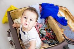 Bebé en una maleta, un viaje Un pequeño niño salió de la maleta y de las miradas en usted Embalado para las vacaciones en centro  foto de archivo libre de regalías