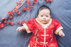 Bebé en vestido rojo en el paño azul con la flor y la mirada Año Nuevo chino del concepto Foto de archivo libre de regalías
