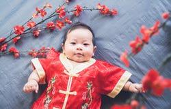Bebé en vestido rojo en el paño azul con la flor y la mirada Año Nuevo chino del concepto Imagenes de archivo