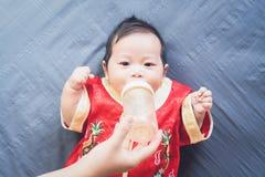 Bebé en vestido rojo en el paño y la leche azules de la consumición Año Nuevo chino del concepto Imagen de archivo libre de regalías