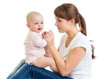 Bebé encantador que parece ausente y que sonríe mientras que se sienta en sus rodillas del ` s de la madre La mamá está mirando a Fotografía de archivo libre de regalías