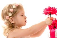 Bebé encantador que sostiene la flor roja Imágenes de archivo libres de regalías