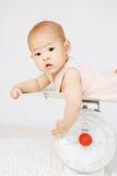 Bebé encendido en balanza  Fotos de archivo