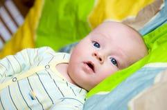 Bebé encendido en cama Imagenes de archivo