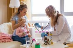 Bebé enfermo de la visita del doctor en casa fotos de archivo libres de regalías