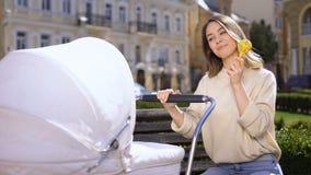 Bebé entretenido femenino sonriente con el juguete del traqueteo, madre joven feliz en parque almacen de video