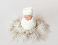 Bebé envuelto en la manta que se sienta en capullo Fotos de archivo