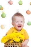 Bebé feliz con las flores de Pascua Imagen de archivo libre de regalías