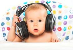 Bebé feliz con los auriculares que escucha la música Imagen de archivo