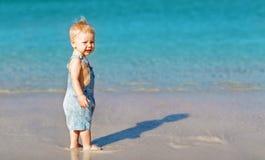 Bebé feliz de la diversión en la playa cerca del mar en verano Imágenes de archivo libres de regalías