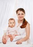 Bebé feliz de la madre de la familia debajo de la cama de las mantas imagen de archivo libre de regalías