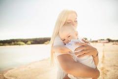 Bebé feliz de los huges de la madre La madre celebra al niño en sus brazos, bebé que abraza a la mamá, primer fotografía de archivo