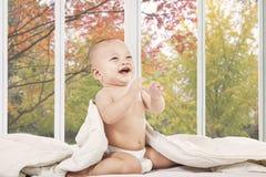 Bebé feliz en dormitorio que ríe solamente imagenes de archivo