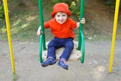 Bebé feliz en el oscilación Imagenes de archivo