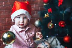 Bebé feliz en el sombrero de Papá Noel s que oculta detrás de una bola contra el árbol de navidad con las decoraciones Bola en fo Fotos de archivo libres de regalías