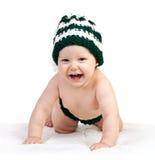 Bebé feliz en el sombrero hecho punto que se arrastra sobre blanco Fotografía de archivo