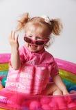 Bebé feliz en la piscina que lleva un traje de baño del flotador Imagen de archivo