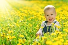 Bebé feliz en prado con las flores amarillas en la naturaleza Foto de archivo
