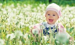 Bebé feliz en prado con las flores blancas en la naturaleza Imagen de archivo