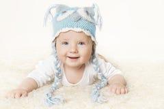 Bebé feliz en sombrero hecho punto azul, muchacho sonriente del niño que aumenta la cabeza fotografía de archivo libre de regalías