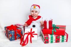 Bebé feliz en traje del muñeco de nieve con las cajas de regalo del regalo de Navidad Fotografía de archivo