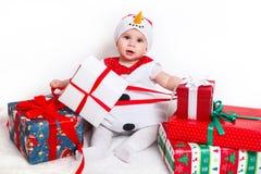 Bebé feliz en traje del muñeco de nieve con las cajas de regalo del regalo de Navidad Imágenes de archivo libres de regalías