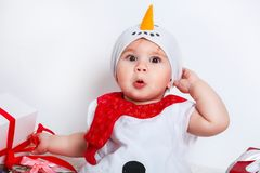 Bebé feliz en traje del muñeco de nieve con las cajas de regalo del regalo de Navidad Foto de archivo