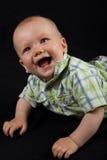Bebé feliz en un fondo negro Foto de archivo libre de regalías