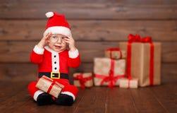 Bebé feliz en un traje Santa Claus de la Navidad con los regalos fotos de archivo libres de regalías