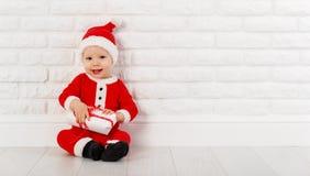 Bebé feliz en un traje Santa Claus de la Navidad con los regalos imagen de archivo