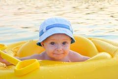 Bebé feliz en una balsa inflable amarilla en la superficie del agua abierta Imágenes de archivo libres de regalías