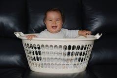 Bebé feliz en una ropa-cesta Foto de archivo