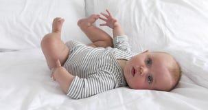 Bebé feliz encantador en la cama blanca almacen de metraje de vídeo