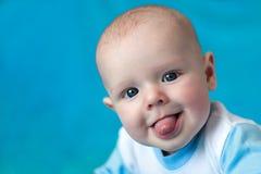 Bebé feliz hermoso que muestra la lengua Imagen de archivo libre de regalías