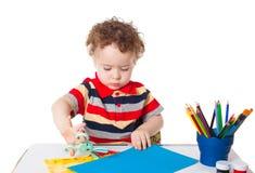 Bebé feliz lindo que corta el papel colorido imagenes de archivo