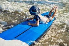 Bebé feliz - paseo joven de la persona que practica surf en la tabla hawaiana con la diversión en el mar Imagen de archivo libre de regalías