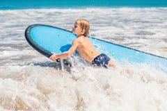 Bebé feliz - paseo joven de la persona que practica surf en la tabla hawaiana con la diversión en el mar imágenes de archivo libres de regalías