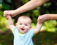 Bebé feliz que aprende caminar en hierba Fotografía de archivo