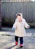 Bebé feliz que corre en la calle Fotos de archivo libres de regalías