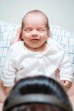 Bebé feliz que descansa en las manos de la mamá después de Brest-alimentar Imagen de archivo