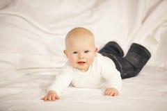 Bebé feliz que encontra-se em um sofá imagem de stock royalty free
