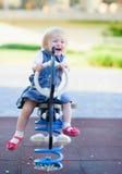 Bebé feliz que hace pivotar en caballo en patio Imágenes de archivo libres de regalías
