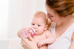 Bebé feliz que introduce Bebé que come la leche de la botella Imagenes de archivo