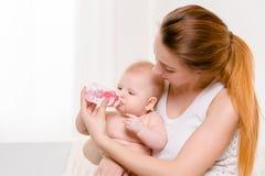 Bebé feliz que introduce Bebé que come la leche de la botella Imágenes de archivo libres de regalías