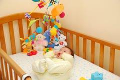 Bebé feliz que juega con el juguete de la cara de la cama Foto de archivo