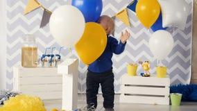 Bebé feliz que juega con los globos en una fiesta de cumpleaños