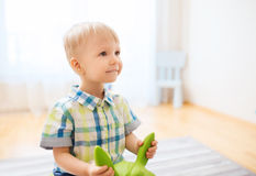 Bebé feliz que juega con paseo-en el juguete en casa Imagenes de archivo