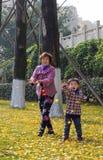 Bebé feliz que juega las hojas de oro del Ginkgo Imagen de archivo libre de regalías