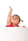 Bebé feliz que lleva a cabo a la tarjeta blanca y que alcanza para arriba imagen de archivo libre de regalías
